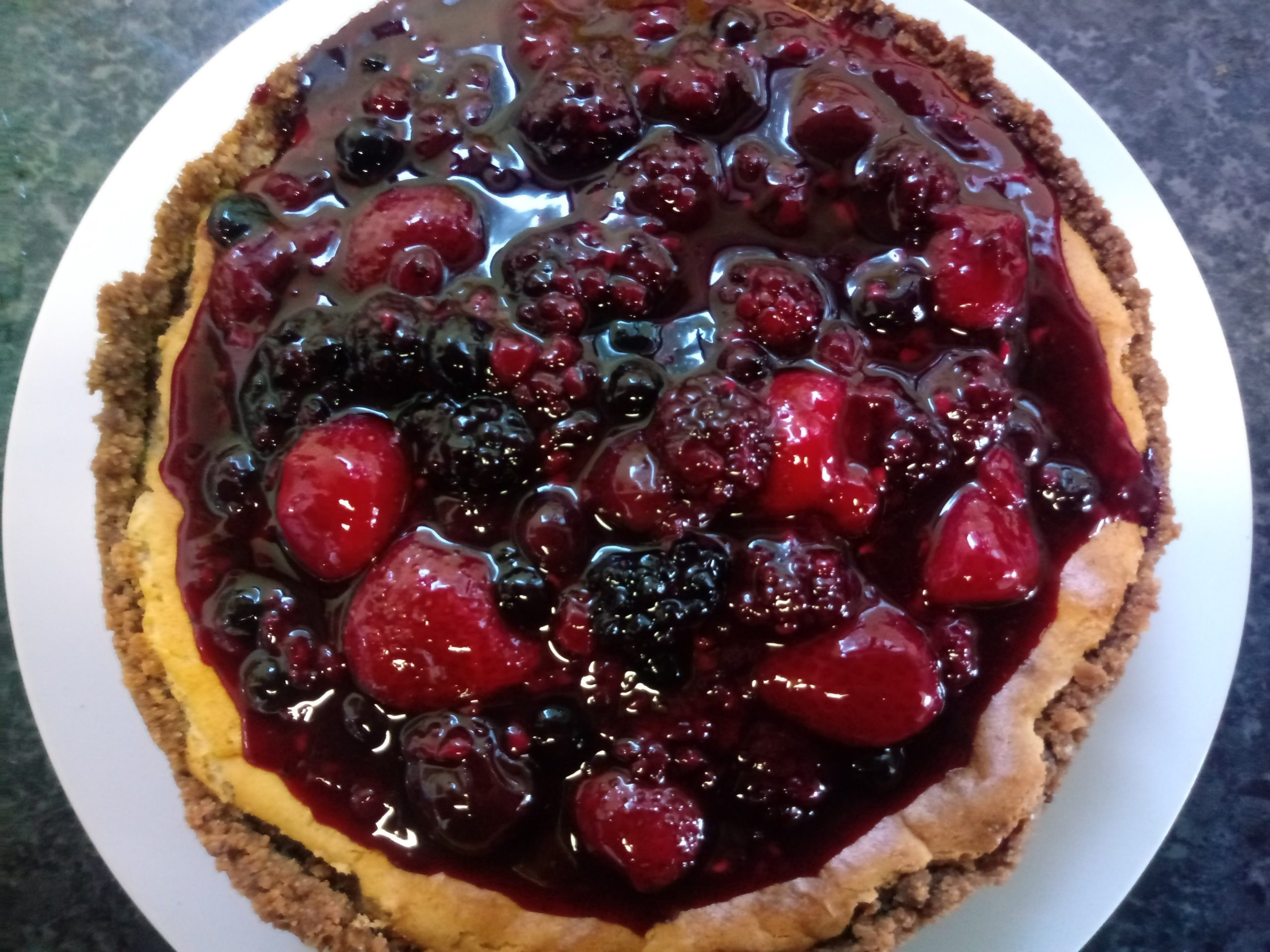 A cheescake made with a biscuit base and a berry compote on top